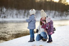 Feeding ducks at winter. Mother and her daughters feeding ducks at winter royalty free stock photo