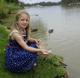 Young Girl Feeding Ducks In The Murray River, Mild Stock Image