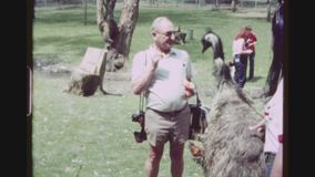 Feeding Emu. AUSTRALIA, SIDNEY. MAY 1980. Two Shot Sequence Of An Older Caucasian Male Tourist Feeding Australias National Bird, An Emu, With Junk Food At The stock footage