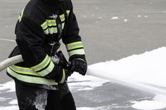 Feeding foam from a handheld fire fighter, fire extinguishing foam flies out of the trunk, which keeps the fireman in combat royalty free stock photography