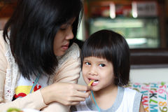 Feeding french fries. Young asian mother feed her daughter french fries Stock Images