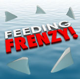 Feeding Frenzy Shark Fins Water Hungry Competition Opponents. Feeding Frenzy in 3d letters on water surface with shark fins surrounding them to illustrate fierce Stock Image