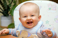 Feeding fun. Happy baby just after feeding. Baby is smiling and sitting on baby's chair royalty free stock images