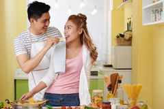 Feeding girlfriend with potato chip. Vietnamese young men feeding his girlfriend when cooking royalty free stock images