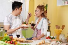 Feeding girlfriend. Young Asian men feeding his pretty girlfriend with spaghetti he made stock photography