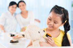 Feeding her teddy bear Stock Image