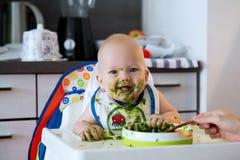 feeding Het Eerste Stevige Voedsel van de baby stock afbeelding