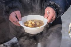 Feeding homeless people on the street. Social problems, hungry people eat stock photo
