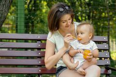 Feeding kid outdoor: infant baby sitting on knees of his mother in summer park and eating vegetable puree from a spoon royalty free stock photos