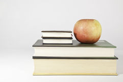 Feeding the mind and stomach. This image shows a few books and an apple. Indicates the need to feed good, the mind, and nourish good the stomach Royalty Free Stock Images