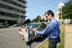 Feeding Parking Meter. Adult business man putting money in a downtown parking meter.  Shot with a Canon 20D Royalty Free Stock Photo