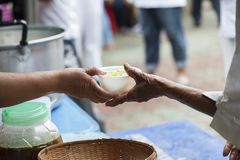 Hands of the poor receive food from the donor`s share. poverty concept. Feeding the poor to help and share stock photos