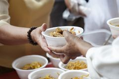 Hands of the poor receive food from the donor`s share. poverty concept. Feeding the poor to help and share stock photo