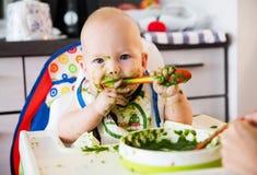 feeding Primer alimento sólido del bebé foto de archivo
