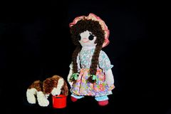 Here Puppy, time for your dinner. New pose. Vintage girl rag doll with her puppy; presented on a plain black background. Feeding the puppy.  Good Puppy here is Stock Photo