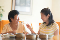 Feeding senior parent food. Asian Chinese adult daughter feeding her senior parent food stock photography