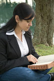 Feeding the Soul. A young woman sitting outside reading or studying what appears to be a bible stock photo