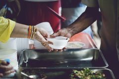 Hands of the poor receive food from the donor`s share. poverty concept. Feeding to hand the poor helping beggar in social. poverty concept royalty free stock photography