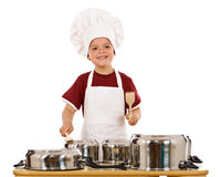 Feel the beat of culinary art. Boy with wooden spoons making some noise banging cooking pots, isolated Royalty Free Stock Photo