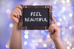 Feel beautiful. A woman holding chalkboard with words feel beautiful on bokeh light background Royalty Free Stock Photos