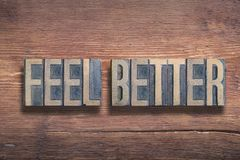 Feel better wood. Feel better phrase combined on vintage varnished wooden surface stock photo