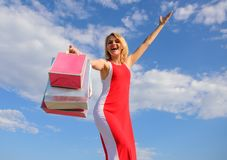 Feel free buy everything you want. Woman red dress carries bunch shopping bags blue sky background. Finally bought. Favorite brands. Tips shop summer sales royalty free stock image