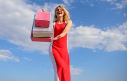 Feel free buy everything you want. Woman red dress carries bunch shopping bags blue sky background. Finally bought. Favorite brands. Girl satisfied with royalty free stock image