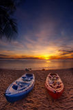 Feel Free. 2 kayaks layin on the beach during sunrise Royalty Free Stock Image