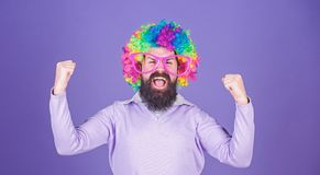 Feel free to express yourself. Having fun. Holiday fun and carnival concept. Man bearded wear colorful wig and funny. Glasses on violet background. Clown and stock photography