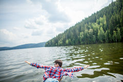 Feel the freedom. Man fooling around at high speed rides on the bow of the boat royalty free stock images