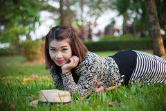 Feel good, be happy & keep smiling. Asian woman smiling on the green grass Stock Photography