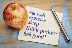 Feel good concept - napkin. Think positive , exercise, eat well, sleep - concept of feeling good - handwriting on a napkin with an apple royalty free stock photos