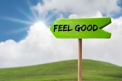 Feel good arrow sign. Feel good green wooden arrow sign on green land with clouds and sunshine stock image