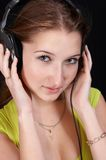 Feel the music. Nice teenager in green on black background with headphones stock images