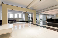 Feel a scent of comfort while you wait. Spacious waiting hall with high-polished tiled floor, tables and sofas Stock Photos