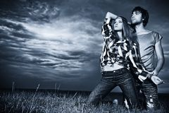 Feel storm. Romantic young couple in casual clothes sitting together in a field on a background of the storm sky Royalty Free Stock Images