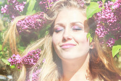 Feel the sunshine on your skin. Portrait of a beautiful girl with lilac flowers and sun rays on the face Royalty Free Stock Photo