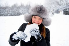 Feel a winterfresh!. Beautiful girl in winter clothing eating ice in the winter woods Royalty Free Stock Image