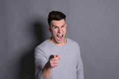 Feeling angry, furious man shouting loud. Feeling angry. Furious man shouting and pointing with his finger to camera on grey studio background Stock Photos