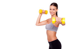Feeling awesome!. Looking even better! Shot of a beautiful and sporty young woman lifting up weights against white background Royalty Free Stock Image
