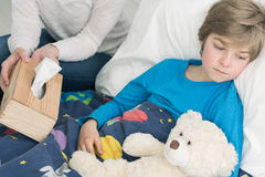 Feeling bad for days. Shot of a sad sick little boy laying on a bed with his teddy bear Stock Photography