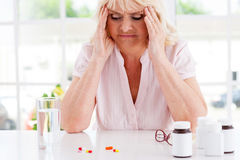 Feeling bad. Depressed senior woman holding head in hands and looking at the pills laying on the table Stock Image
