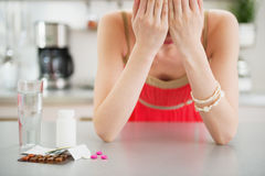 Feeling bad girl and pills on table Stock Images