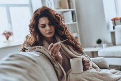 Feeling bad. Sick young woman looking at thermometer while sitting on the sofa at home Royalty Free Stock Image