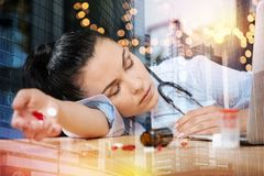 Exhausted doctor falling asleep while being at work and holding pills. Feeling bad. Tired young doctor feeling unwell and having a nap at her workplace with Stock Photography