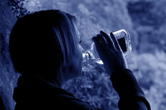 Feeling Blue. Head and shoulders outdoor close up in blue of young woman drinking from a spirit bottle stock images