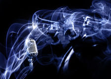 Feeling the blues. Smoke wrapping an old fashioned microphone and morphing to a trumpeter playing his music Stock Images