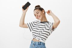 Feeling boost of happiness from hearing great songs in earbuds. Pleased feminine girl in striped t-shirt, dancing with. Raised hands, holding smartphone stock images