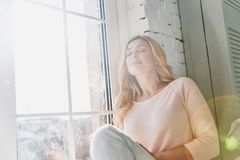 Feeling calm and happy. Attractive young woman keeping eyes closed and smiling while sitting on the window sill at home stock image