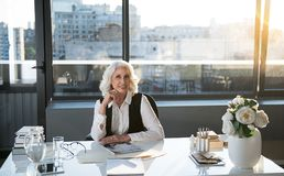 Elegant optimistic old woman is enjoying her work Royalty Free Stock Photography